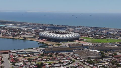 Wide static aerial view of traffic on roads in Port Elizabeth, travelling around the Nelson Mandela Bay Stadium area. Industrial area and ships at sea visible in background