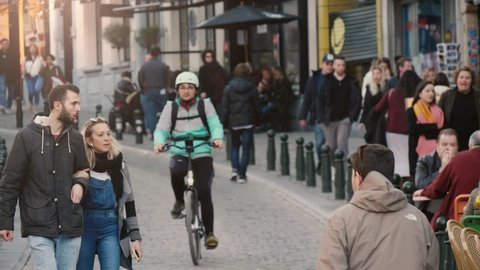 Bruges, Belgium - March 31, 2019:Optimistic view of smiling strolling people, riding bicycles, moving cars in cobblestone street in Brussels in spring in slow motion.