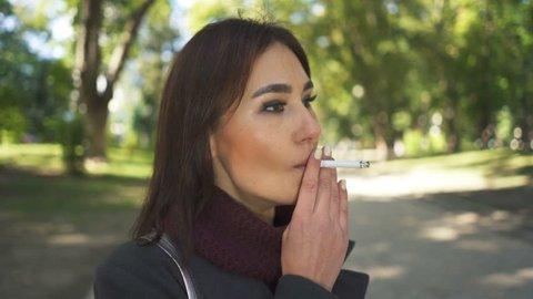 Asian girl  smokes a cigarette in park, looking at camera.
