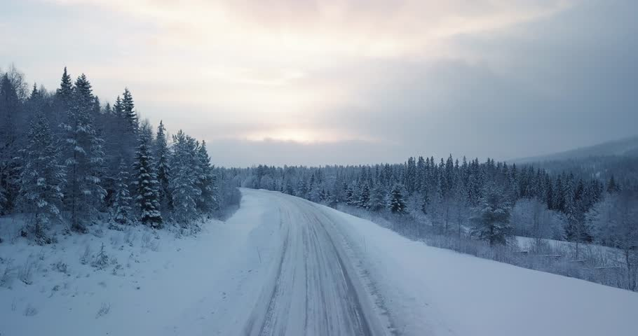 Aerial of car driving in winter paradise in Norway. Surrounded by snow and trees. | Shutterstock HD Video #1028222978