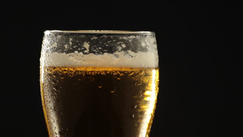 Close-up of cold glass with water drops. Cold light beer with bubbles in a glass and dripping condensate drops. Glass of cold beer slowly rotates around its axis.  | Shutterstock HD Video #1028229368