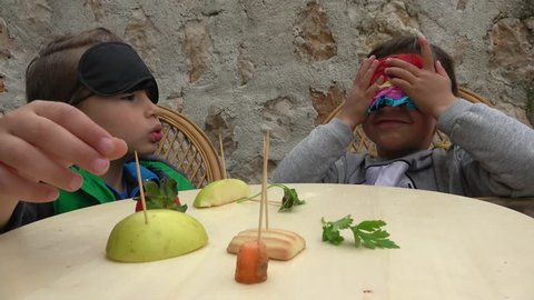 Fethiye, Turkey - 7th of April 2019: Guess what food challenge - 4K 4K Two boys play blindfold in guess what food, cryctal child