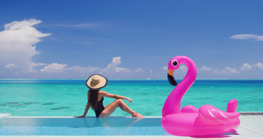 Summer Vacation Woman in bikini and inflatable pink flamingo pool toy mattress in swimming pool. Elegant lady relaxing sunbathing enjoying travel holidays at resort pool. Luxury lifestyle. | Shutterstock HD Video #1028273588