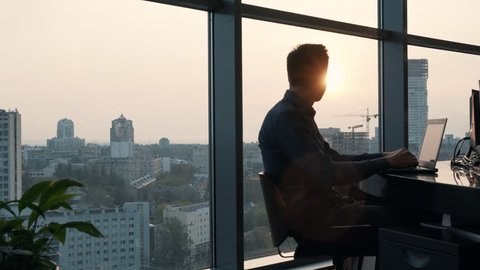 Man Working On Modern Office At Sunrise.Overtime Work In Office.Overtime Work In Office.Creative Man With Computer Working At Office In Sunset.Businessman Working Alone .Work In Morning.