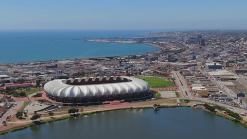 Port Elizabeth, South Africa - circa 2010: Aerial fly over. Central Business District and active port on a sunny summer day. Nelson Mandela Bay Stadium, North End Lake and industrial area close by.