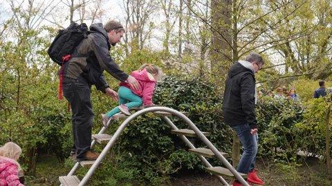 KEUKENHOF PARK, NETHERLANDS - APR 13, 2019: People enjoy climbing stairs attraction during walking in a park having fun