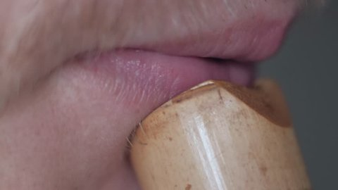 Macro shoot - Male flutist playing on bamboo flute close up. Lips of the playing musician of the flute player close-up.