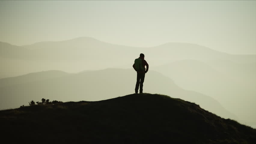 Silhouette of Caucasian European female adventure hiker on her vacation trekking on the top of mountain Snowdonia National Park Wales RED MONSTRO #1028326298