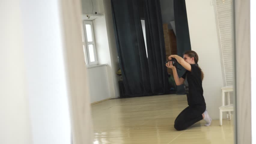 Young female photographer in black clothes sitting on the floor and taking pictures in professional photo studio. Media. Professional photo session | Shutterstock HD Video #1028339228