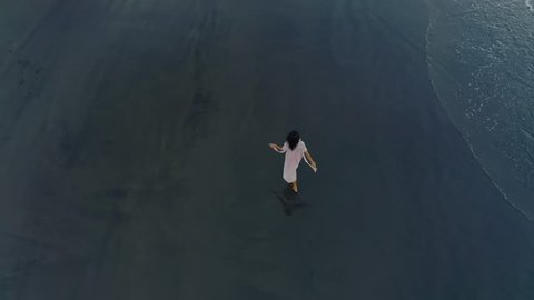 Self-Sufficient Idyll. Slender Brunette Walking on the black Sandy Beach and soft sea surf. Flying around the Girl Moving to Meet the Ocean. Aerial View From Drone 4K