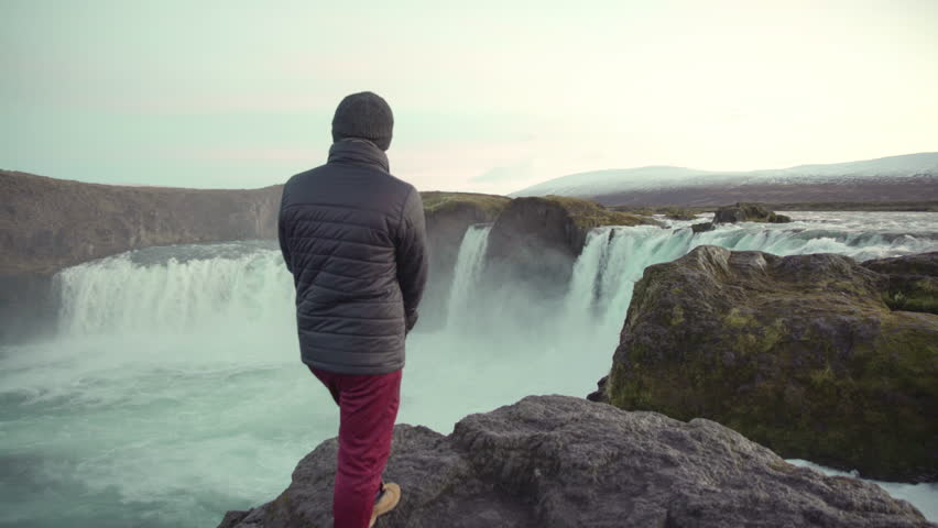 Man standing over the Godafoss Waterfall in Iceland | Shutterstock HD Video #1028355188