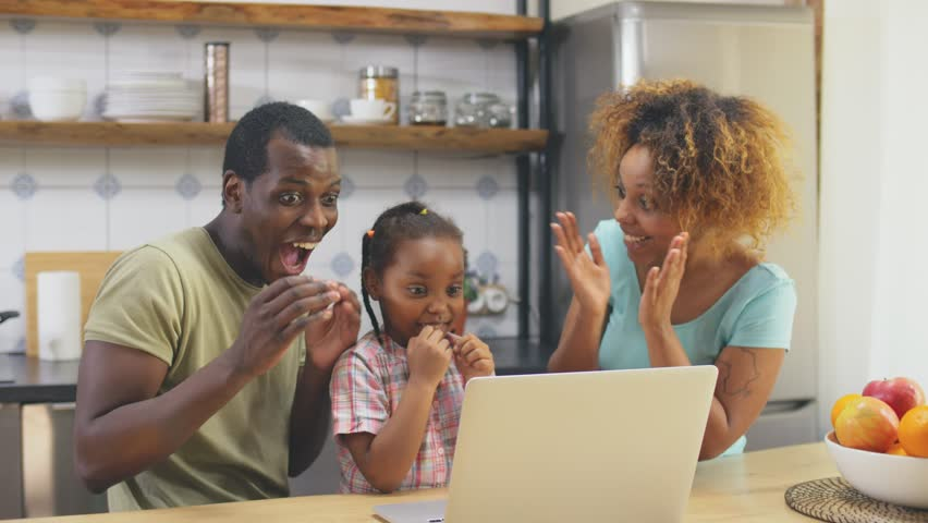 Little girl playing computer game on laptop with her parents. They rejoice at her victory. | Shutterstock HD Video #1028372258