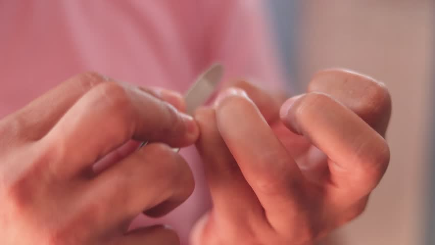 Close up man filing nail with nail file #1028383658