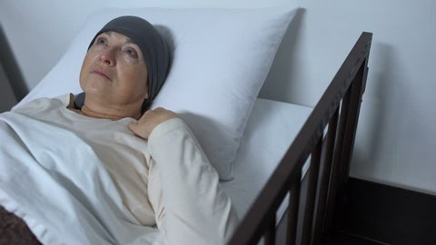 Depressed female patient suffering cancer lying in sickbed, incurable disease