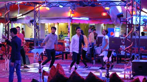 EGYPT, SHARM EL SHEIKH, APRIL 8, 2019: Egyptian mans dance for tourists in the street restaurant at Naama Bay. Slow Motion. Traditional Cafe in Egypt with dancing guys Pj.