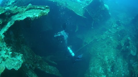 Two divers on wreck covered with rust, metal corrosion and corals underwater on seabed of Pacific Ocean on Chuuk Islands. Sunken ship in historic place of terrible tragedy of WW II.