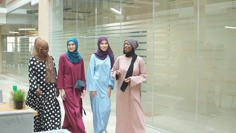 A group of four young muslim multiethnic business women dressed in fashionable tradition dresses chatting and walking together in business centre