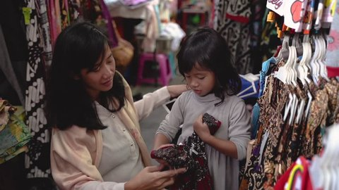 indonesian mother buy and try batik for her daughter in tradtional market