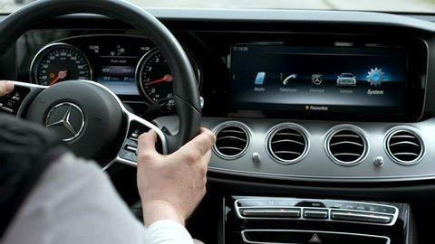 Berlin, Germany - April 16, 2019: Man testing additional car control at Mersedes E 213 car dashboard using modern sensor button on te wheel