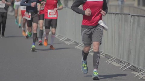 Close-up of athletes' legs running long-distance marathon. A crowd of athletes and sports enthusiasts take part in the marathon for a long distance. Warsaw Poland.