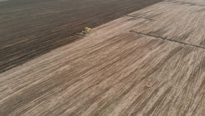 large yellow tractor cultivates field after harvesting grain crops? Agronomic activities on farm