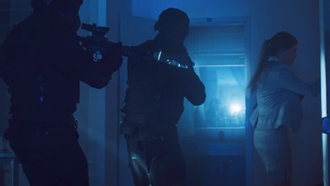 Masked Squad of Armed SWAT Police Officers Rescue a Female Hostage in a Dark Seized Office Building with Desks and Computers. Soldiers with Rifles and Flashlights Move Forwards and Cover Surroundings.