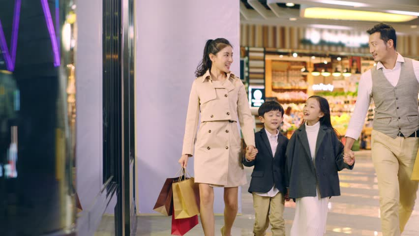 happy asian family with two children walking hand in hand in shopping mall