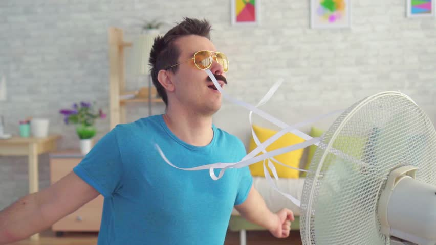 Funny young man in front of a working electric fan escapes from the heat in the apartment slow mo | Shutterstock HD Video #1028604668