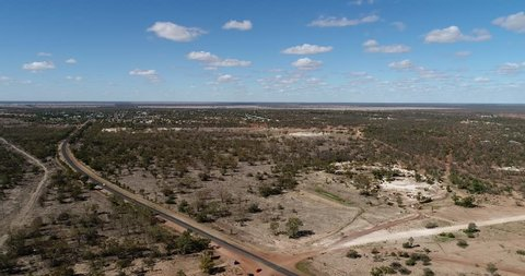 Flat arid plains of Australian outback with red soil around Lightning Ridge opal mining town in elevated aerial flying over a road connecting town to highway.