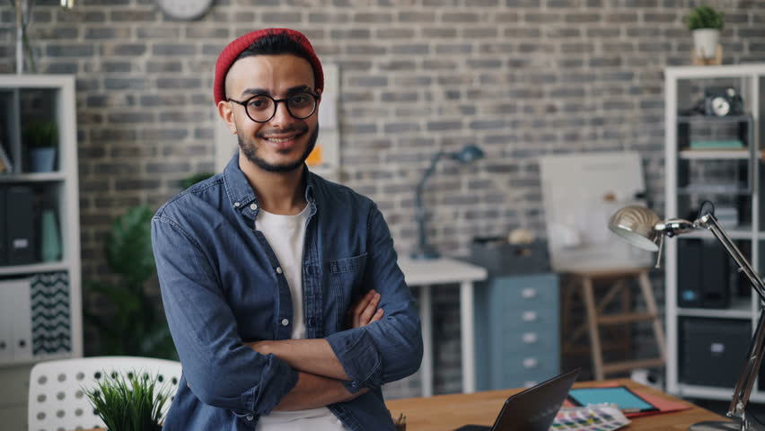 Portrait of happy business owner good-looking bearded guy standing in creative office with arms crossed smiling and looking at camera. People and workplace concept.
