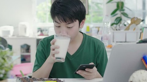 Asian young boy using scrolls through smartphone applications, while slowly eats organic milk breakfast with bread biscuit and chocolate at home.