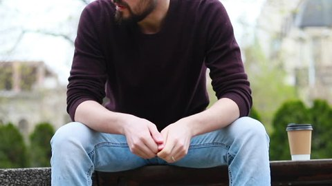 man sitting on hospital garden bench, pensioner crying in sorrow. A sad handsome man sitting on a bench waiting for someone on a sunny day. Depressed guy is alone in a park.