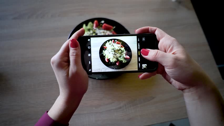 Young woman in a restaurant make photo of food with mobile phone camera. Woman make photo of salad | Shutterstock HD Video #1028794508