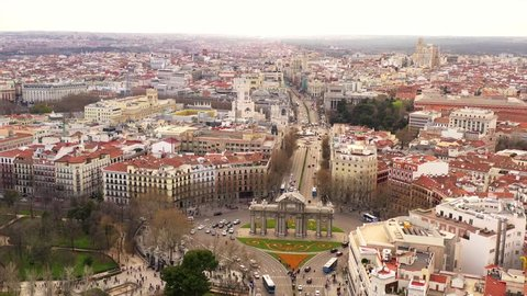 Busy Puerta de Alcalá in Madrid. Cars are driving on the street and pedestrians are entering and leaving the park El Retiro. The scenery is shown in an aerial shot on a semi cloudy day.