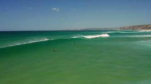 Aerial: Surfing the beach of Bordeira in the Algarve, Portugal.