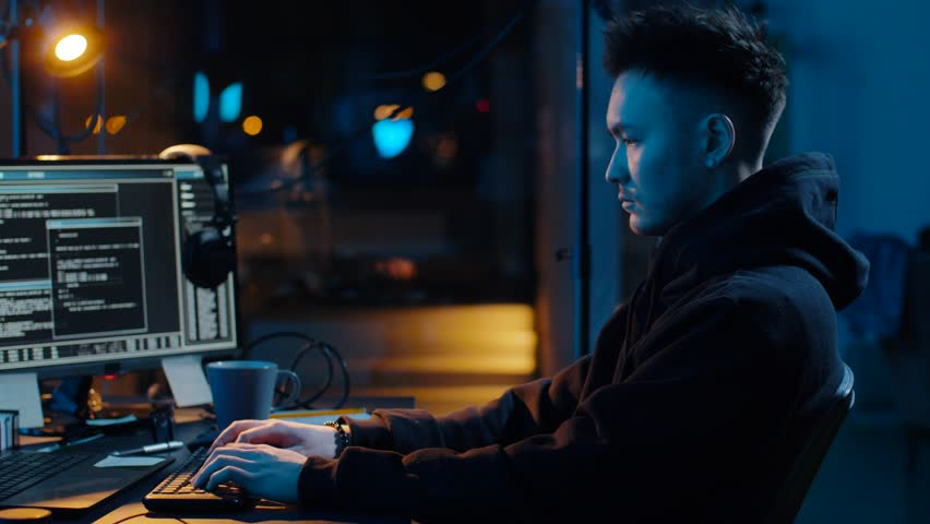 Cybercrime, hacking and technology concept - asian male hacker writing code or using computer virus program for cyber attack and drinking coffee in dark room at night | Shutterstock HD Video #1028826698