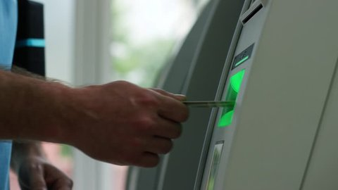 Unrecognizable man using an ATM machine. Outdoors. Inserting card in the cash machine. Money, finance, cash. Inserting credit debit card in cash dispenser. Close up view