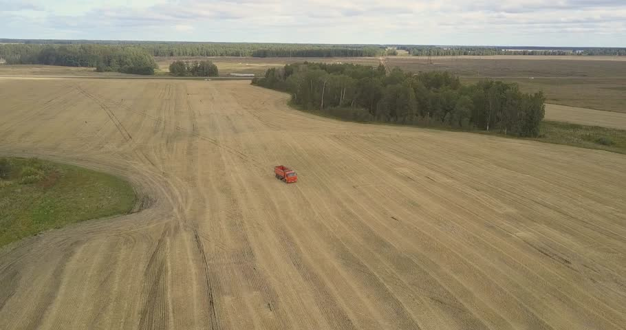 beautiful bird eye view empty red truck drives along harvested autumn field to reaper thresher