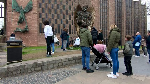 Coventry, West Midlands, UK - April 7, 2019: People looking and taking photographs of a statue outside Coventry cathedral