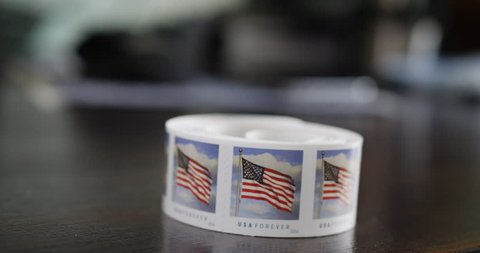 Close up shot of a business office desk with an employee tearing off some American flag forever stamps to mail some documents.