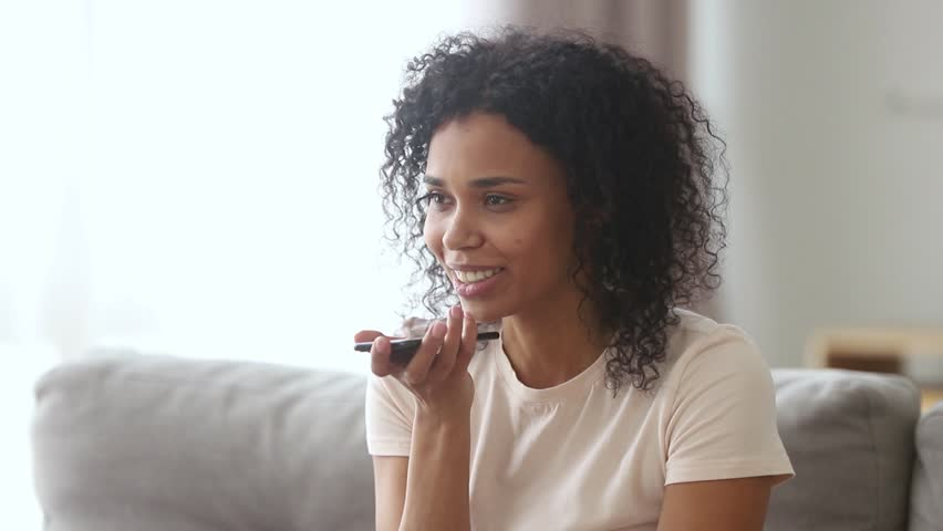 Happy african american woman holding phone activate virtual digital voice assistant on smartphone ask to make call sitting on sofa at home, easy internet service, ai intelligent technology assistance