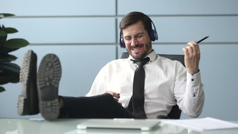 Happy funky businessman relaxing wearing wireless headphones listening to music pretending playing guitar at workplace, funny male worker enjoy favorite track having fun during work break in office