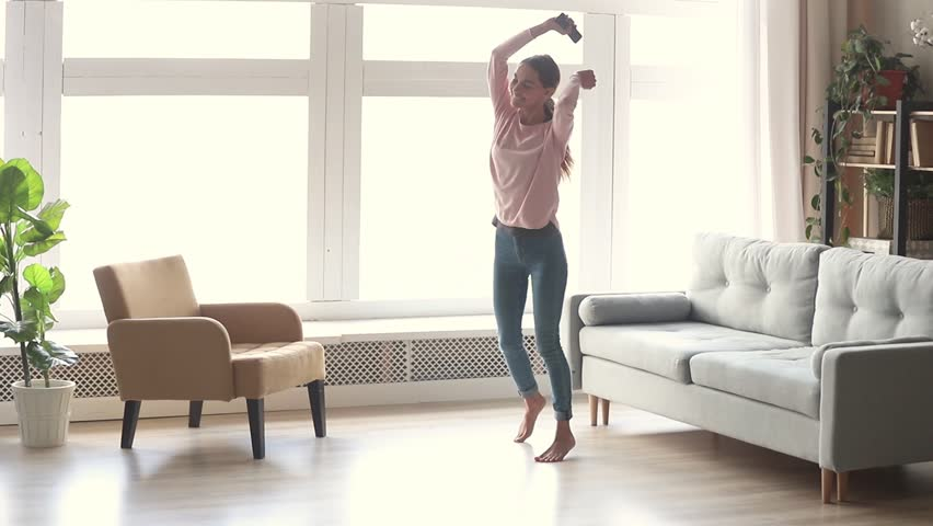 Happy carefree young woman dancing alone in modern living room with big window listen to music on smartphone, funky millennial girl holding phone enjoy new hit song playing in app having fun at home