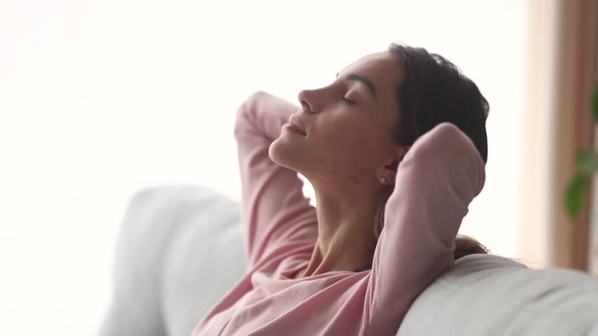 Calm young woman relax with eyes closed take deep breath of fresh air dream nap on couch, healthy girl rest on sofa enjoy meditation do yoga exercises feel stress relief peace of mind lounge at home | Shutterstock HD Video #1028900258