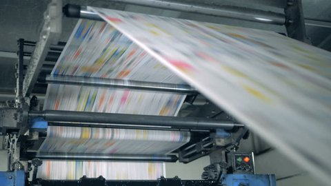 A machine works, rolling printed newspaper in typography facility
