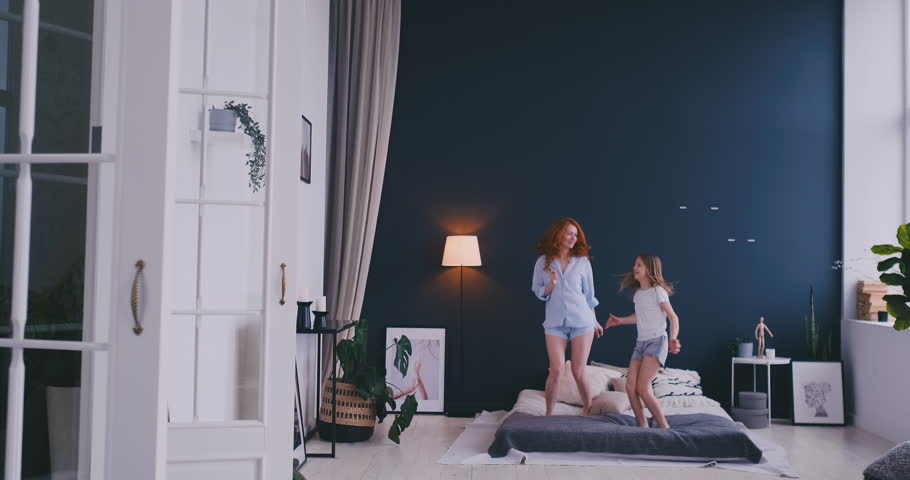 Cute little girl with her loving mother have fun dancing modern style together jumping and giving high five on bed during morning in cozy bedroom at home #1028919938