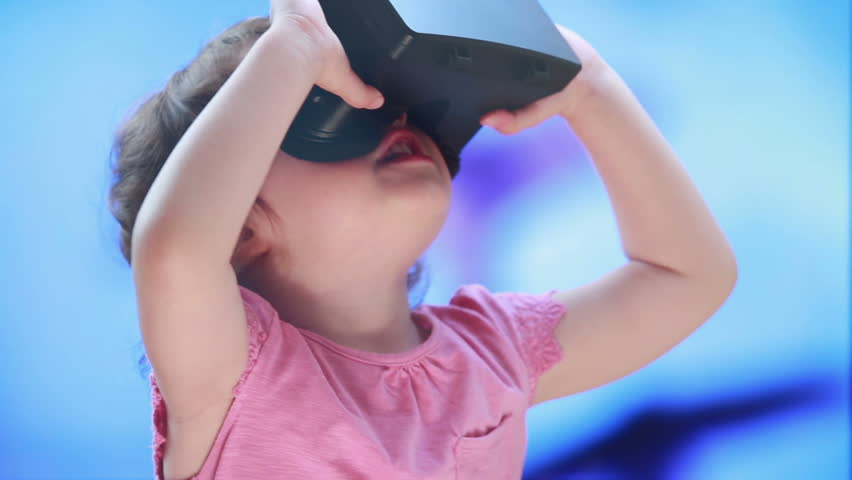 Virtual reality game. The little girl with surprise and pleasure uses head-mounted display. | Shutterstock HD Video #10289354