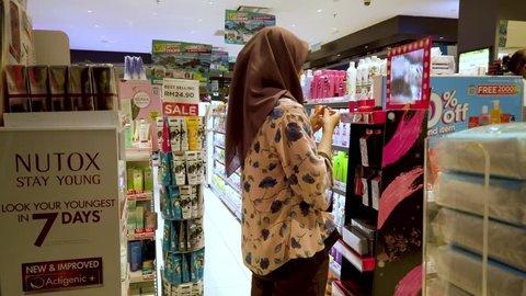 KUALA LUMPUR,MALAYSIA-CIRCA APRIL,2019 : Woman at Watson pharmacy using tester and buying cosmetic.
