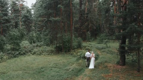 Couple in wedding dress walks through the woods. Green Forest. Couple walks between the trees. Wedding dress at the bride. Wedding walk. Wedding. Married