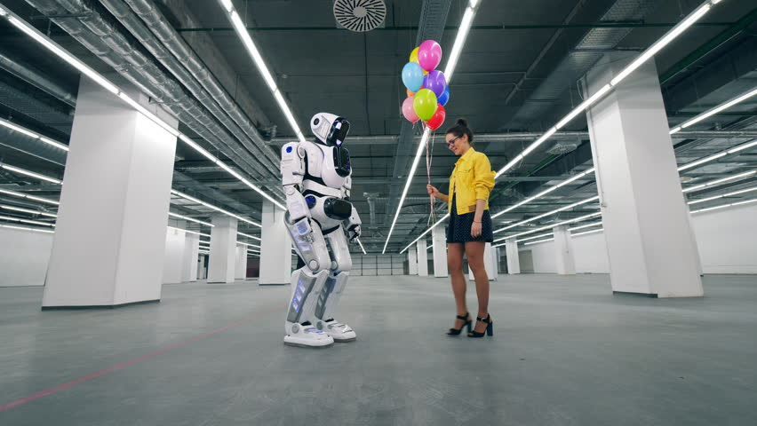 Young woman is gifting balloons to a tall robot | Shutterstock HD Video #1028988488